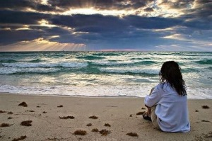 Sad-girl-alone-sitting-in-beach-watching-waves-image-picture-1111x738