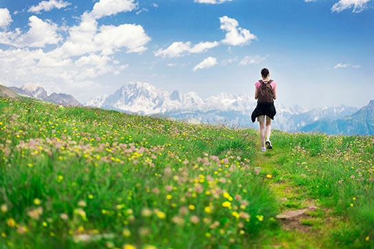 woman-hiking-in-meadow-toward-mountains